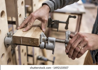 Using clamps and glue to connect wooden timbers for furniture detail. Joiner making a furniture.