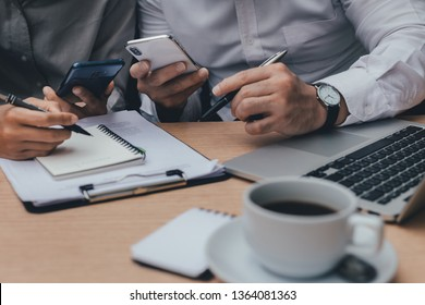 using computer,laptop,cell phone.business financing partner Thinking and discussing something about business investment plan sitting at office desk.Contact finance in modern communication