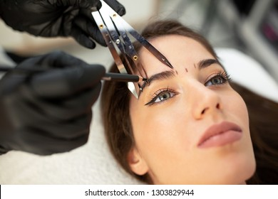 Using cosmetics tools for taking the correct measure of future eyebrows done with microblading technique