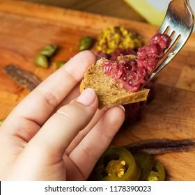 Using fork for placing Tartara steak on a bread see more Tartara or Tatar in gallery
