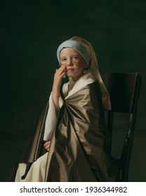 Using golden eye patches. Medieval little girl as lady with a pearl earring on dark studio background. Concept of comparison of eras, childhood, ancient. Stylish, creative, art vision, new look.