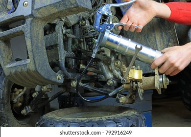 Using Grease Gun To Lubricate Suspension Joints On A Quad Bike. Routine Repair Maintenance In A Workshop.