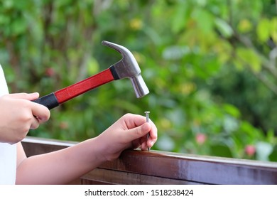 Using hammer and nail on wood and bokeh background.