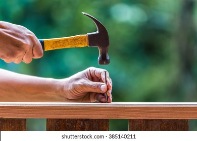 Using hammer and nail on wood and bokeh background