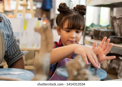 Using hands. Dark-eyed schoolgirl with nice hairstyle using her hands while sculpting clay figures