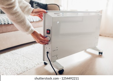 Using heater at home in winter. Woman regulating temperature on heater. Heating season.
