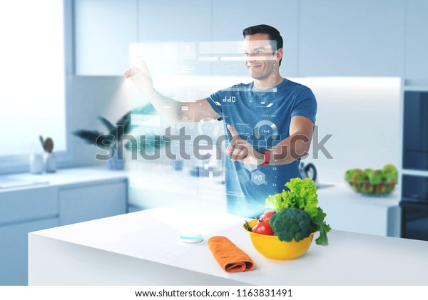 Using holograms. Handsome young cook smiling and touching the hologram while checking the recipe for a delicious meal