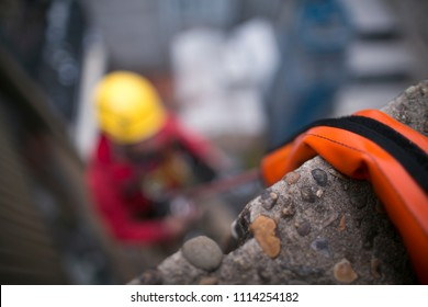 Using industry heavy duty orange safety rope protection to protecting damaging from sharp edge corner with unfocused  abseiler at the background at construction ้high rise building site Sydney CBD