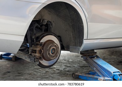 Using a jack to lift the vehicle to remove the wheel.