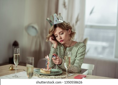 Using lighter. Birthday woman using lighter while burning the candle on piece of cake staying alone