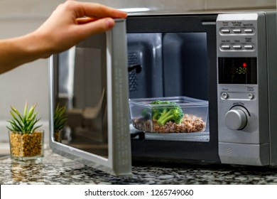 Using the microwave oven to heat food. Heating plastic container with broccoli and buckwheat in the microwave