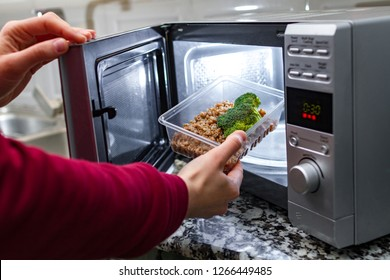 Using the microwave oven to heat food. Woman's hand puts plastic container with broccoli and buckwheat in the microwave