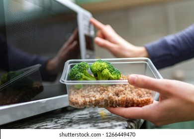 Using the microwave oven to heating food. Woman's hand going to heat up a plastic container with broccoli and buckwheat in the microwave