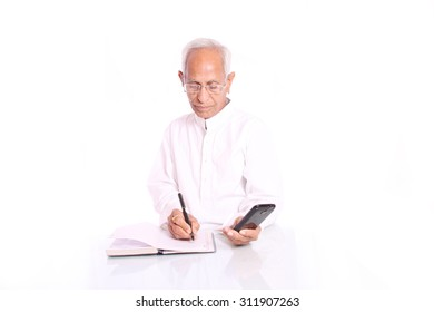 Using mobile phone, an old man calculating and writing over diary, photographed this picture against white background
