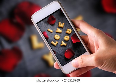 using mobile phone to take photos of Cookies ABC in the form of word I LOVE YOU alphabet  with red rose petal on old jean background, Valentines day