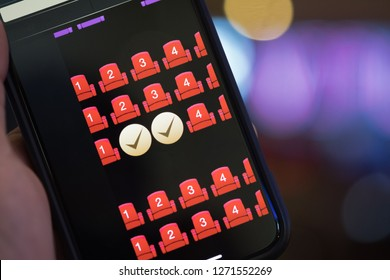 Using mobile smart phone buy cinema tickets, reserved seating, online booking and payment concept