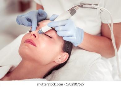 L'utilisation d'équipements modernes. Cosmetologue portant des gants utilisant des équipements modernes pour le nettoyage du visage