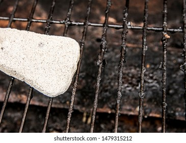 Using natural pumice stone to scrub charred food deposits and rust from BBQ grill metal grid. Safe way to clean grill concept.