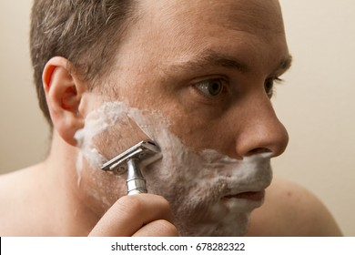 Using an old fashion safety razor man is shaving his face