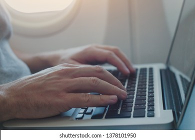 using onboard internet on laptop in airplane, passenger working on computer in  plane, closeup of hands typing on keyboard inside aircraft