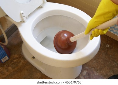 Using a plunger in the toilet. Healthy lifestyle, home, cleaning and organizing, everyday living concepts.