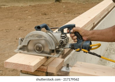 Using a power circular saw to trim the top plate board of a stud lumber wall  on a new luxury custom home