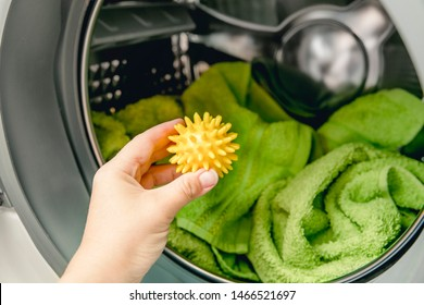 Using pvc dryer balls is natural alternative to both dryer sheets and liquid fabric softener, balls help prevent laundry from clumping in the dryer.  Woman hand put in a yellow spiky dryer ball.