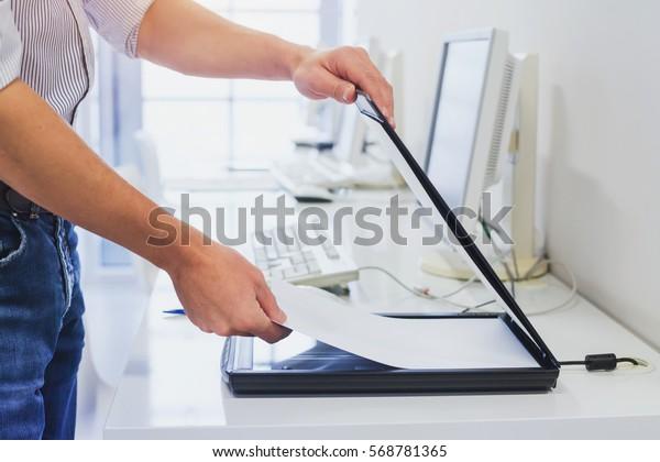 использование сканера в офисе или библиотеке, крупным планом рук сканирование документов