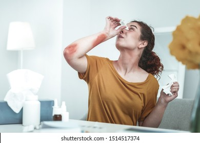Using self-medication. Curly red-haired woman using self-medication while having strong allergy