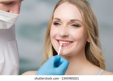 Using shade guide at womans mouth to check veneer of tooth crown
