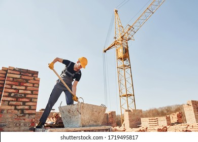 Using showel. Construction worker in uniform and safety equipment have job on building.