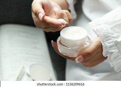 using a skin care product, moisturizer or lotion taking care of her dry complexion. Moisturizing cream in female hands .