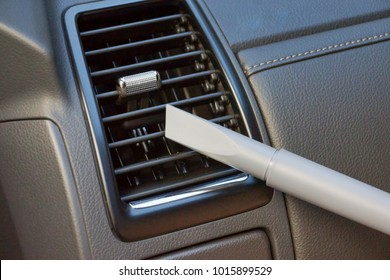 Using a small vaccum cleaner head to clean air conditioner in a car
