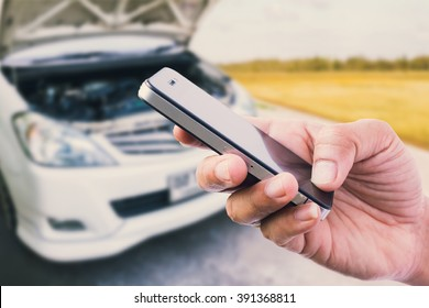 using smart phone with broken car background