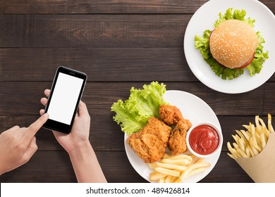Using smart phone with burger, french fries and fried chicken set on wooden background.