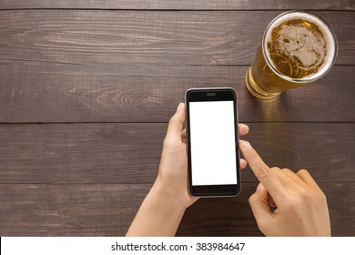 Using smartphone beside of beer in the pub.