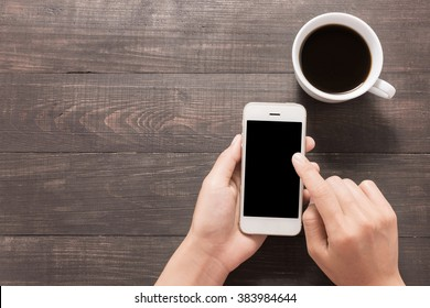 Using smartphone beside of coffee on wooden table.
