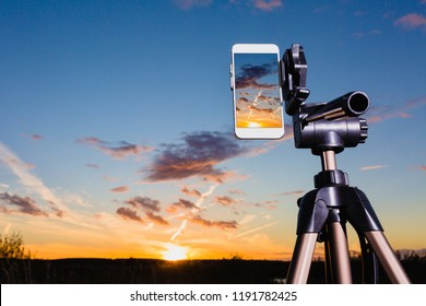 Using smartphone on tripod to capturing image of stunning sundown in vertical mode
