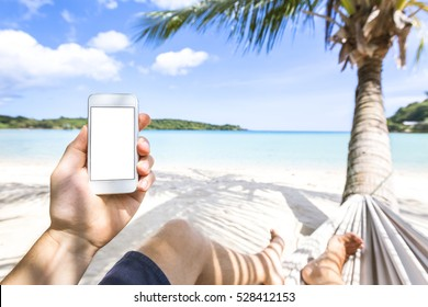 Using smartphone on a tropical paradise beach sitting in hammock, mobile phone and technology during sea holidays