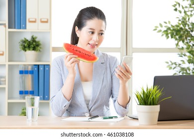 using smartphone to text message and having fresh watermelon