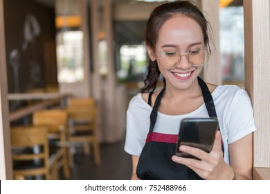 using smartphone.woman smiling wears white shirt and black apron and holding smart phone in owner business shop,Enjoying and Smiling waitress work on cafe and restaurant