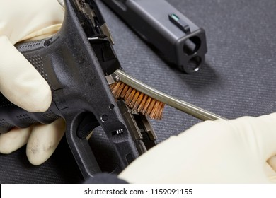 Using a steel brush to clean the parts to a handgun with shallow depth of field