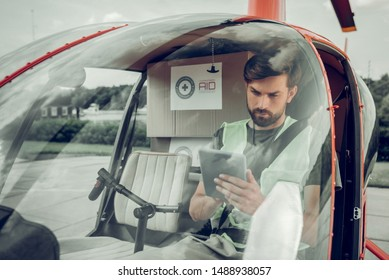 Using tablet. Bearded pilot wearing bright vest using his tablet while sitting in little helicopter