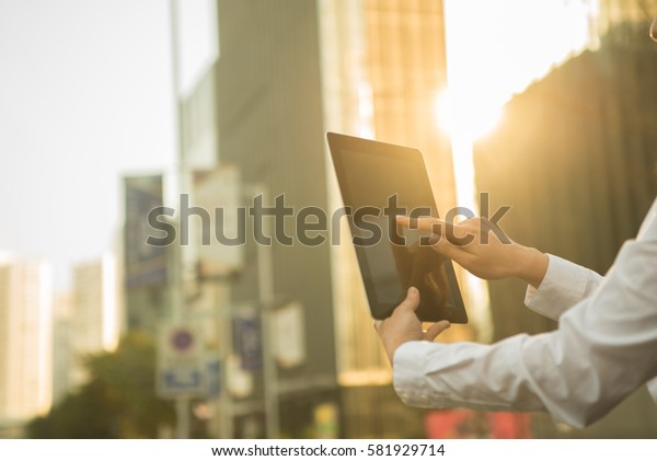 using tablet during sunset with skyscraper