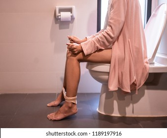 Using toilet. Woman in bath towel sitting on toilet bowl