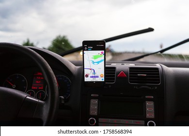 Using waze maps application on smartphone on car dashboard, Driver using maps app for showing the right route through the traffic of city at sunset on a rainy evening. Bucharest, Romania, 2020.