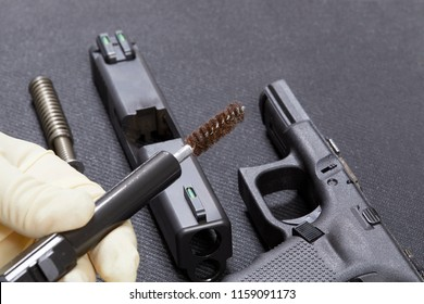 Using a wire brush to clean the parts to a handgun with shallow depth of field