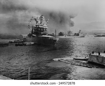 USS California lists after aerial blows taken during the Japanese attack on Pearl Harbor. In distance the USS Neosho, cautiously backs away from berth, avoiding capsized USS Oklahoma. Dec. 7, 1941.