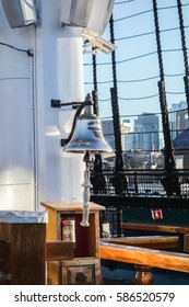 USS Constitution ship bell, mast, rigging, and Boston city skyline.