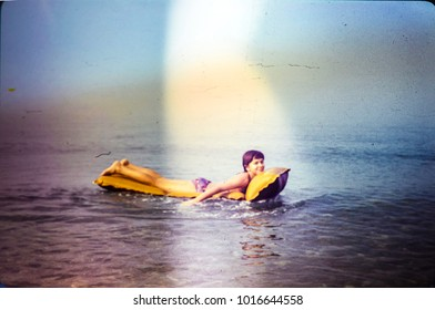 USSR, ABKHAZIA, BLACK SEA - CIRCA 1981: Vintage photo of young girl floats on an inflatable mattress